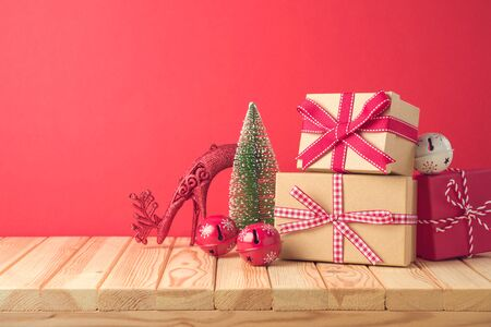 Christmas holiday celebration concept with gift boxes and pine tree on wooden table. Imagens