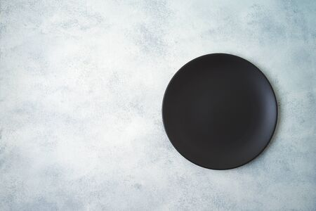 Empty black plate on gray stone table background. Top view from above Фото со стока - 131364078