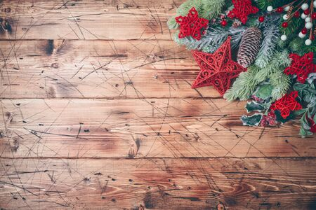 Christmas background with fir tree branches and red stars decorations on wooden table. Top view from above Imagens