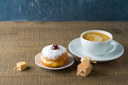 Food and drink concept. Coffee cup with traditional donuts sufganiyah for Hanukkah on wooden table. Stock Photo