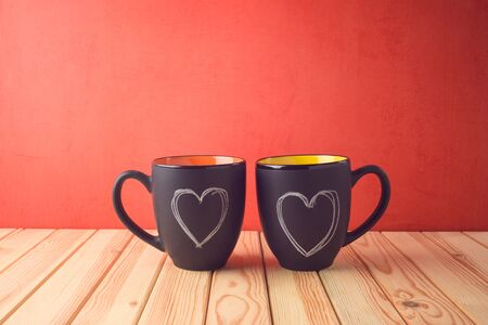 Valentines day concept with chalkboard coffee mugs and heart shapes on wooden table. Stock Photo - 137448440