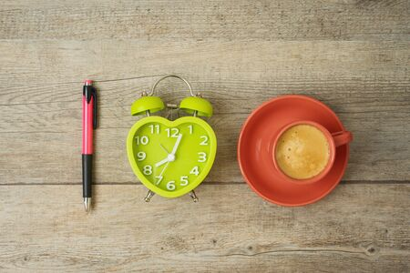 Coffee break concept. Coffee cup, alarm clock and pen on wooden background. Top view from above