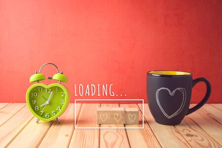 Valentines day concept with chalkboard coffee mugs, heart shape, alarm clock and  loading love text on wooden table. Archivio Fotografico - 138047755
