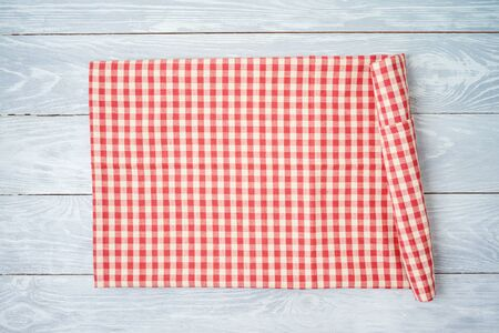 Red checked tablecloth on rustic wooden table. Kitchen, cooking or baking mock up background for design. Top view from above