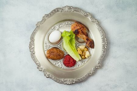 Jewish holiday Passover celebration concept with traditional seder plate over rustic background. Top view from above.