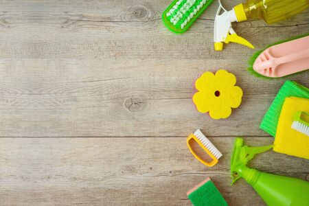 Spring cleaning concept with supplies over wooden background. Top view from above