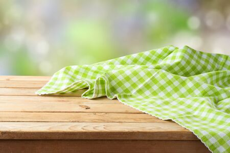 Empty wooden table with green checked tablecloth over green bokeh background.