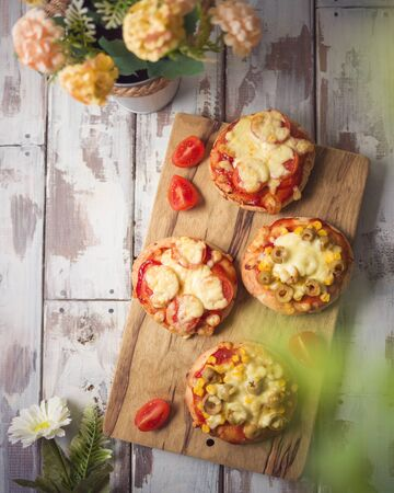 Mini pizza on wooden board. Top view from above