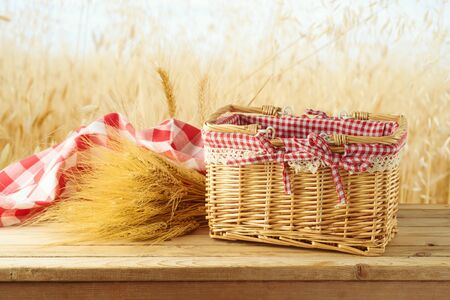 Empty picnic basket with wheat and red checked tablecloth on wooden table over blurred wheat field background. Harvest mock up for design.