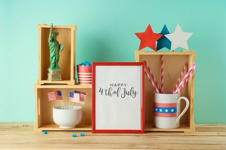 Happy Independence Day, 4th of July celebration concept with photo frame and patriotic home decor on wooden table Фото со стока