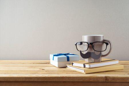 父亲节快乐的概念与咖啡杯,胡子和礼盒在木桌上