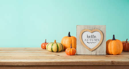 Hello Autumn concept with photo frame and pumpkin decor on wooden table over blue background. Fall season greeting card. Фото со стока