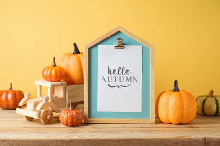 Hello Autumn concept with pictute frame, toy truck and pumpkin decor on wooden table over yellow background. Fall season greeting card. Фото со стока