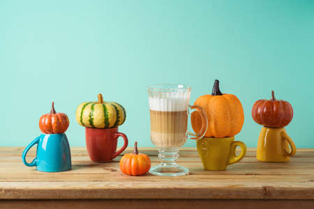 Autumn season creative concept with latte macchiato coffee cup and pumpkin decor on wooden table. Thanksgiving greeting card.