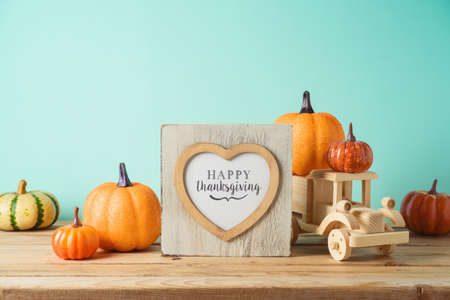 Happy Thanksgiving concept with photo frame, toy truck and pumpkin decor on wooden table over blue background. Autumn season greeting card. Фото со стока
