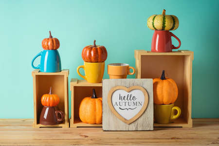 Hello Autumn concept with heart shape photo frame and pumpkin decor on wooden table over blue background. Фото со стока