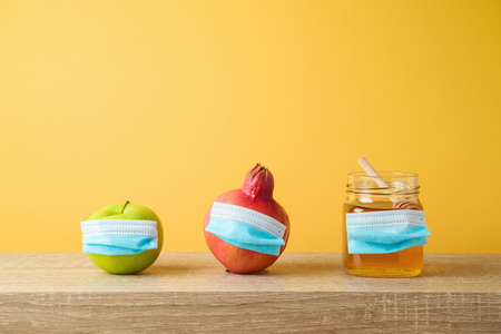 Jewish holiday Rosh Hashana concept with honey jar, apple and pomegranate with face medical mask on wooden table. Holiday celebration new normal greeting card 免版税图像