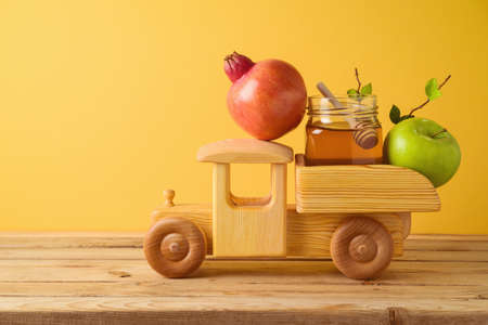 Jewish holiday Rosh Hashana concept with toy truck, honey, pomegranate and apples on wooden table over yellow background 免版税图像