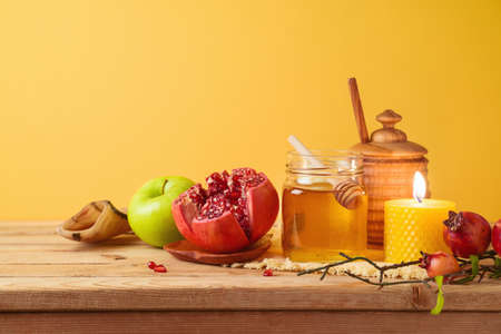 Jewish holiday Rosh Hashana concept with honey jar, apple and pomegranate on wooden table over yellow background