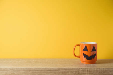 Kitchen wooden shelf background and orange coffee cup with jack o lantern spooky face. Halloween holiday decor concept