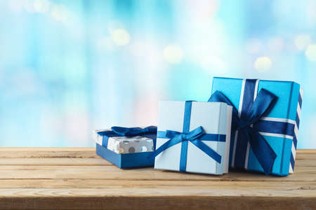 Blue gift boxes on wooden table. Christmas or Hanukkah celebration concept.