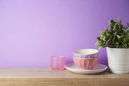 Kitchen utensils and dishware on wooden shelf. Kitchen interior purple background