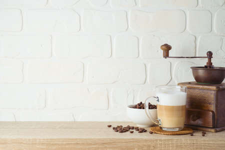 Kitchen background with coffee cup and coffee mill grinder on wooden shelf 免版税图像