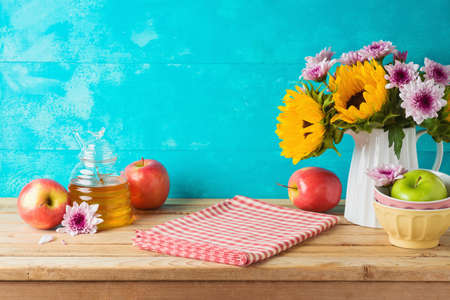 Honey jar, apples and sunflowers on wooden table. Kitchen counter with tablecloth and copy space for product display 免版税图像
