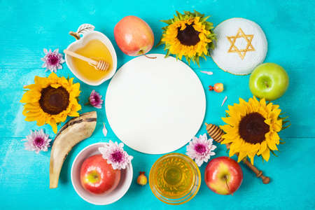 Jewish holiday Rosh Hashana background with honey, apples and sunflowers on blue wooden table. Top view from above 免版税图像