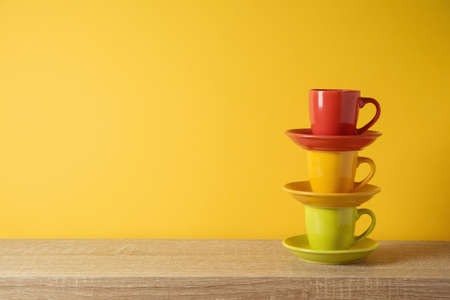 Coffee cups on wooden shelf over yellow wall background 免版税图像
