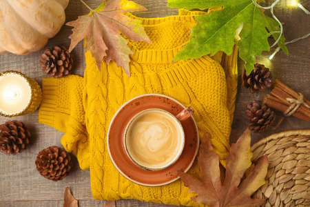 Autumn season concept with coffee cup, warm sweater, pumpkin and fall leaves. Hygge background 免版税图像