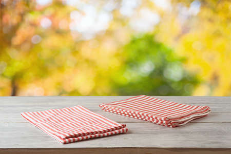 Empty wooden table with striped tablecloth over autumn bokeh background. Food or product display mock up for design.
