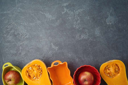 Autumn season cooking and baking background with cake pans, apples and pumpkin on stone tabletop 免版税图像