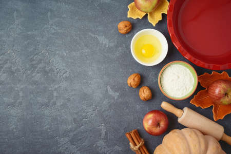 Thanksgiving day cooking and baking background with apples and pumpkin pie ingredients 免版税图像