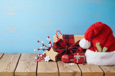 Christmas holiday background with Santa hat, gift boxes and decorations on wooden table