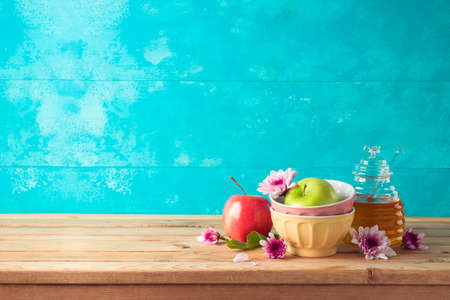 Jewish holiday Rosh Hashana background with honey jar, apple and flowers on wooden table