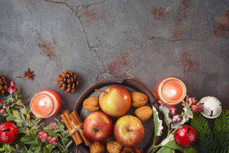 Christmas background with apples, walnuts and candles on stone tabletop. Holidays cooking and baking concept 免版税图像
