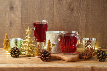 Christmas mulled red wine with spices and Christmas decorations on wooden table. Happy holidays greeting card. 免版税图像