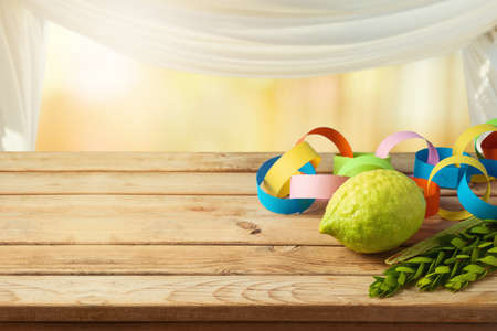 Jewish holiday Sukkot celebration background with decorations on wooden table