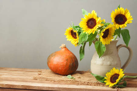Autumn background with sunflowers and pumpkin on wooden table