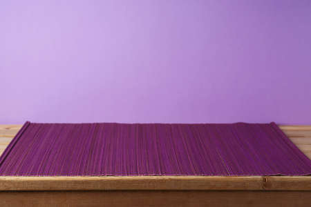 Empty wooden table with bamboo mat over purple background. Kitchen or restaurant counter mockup for design 免版税图像