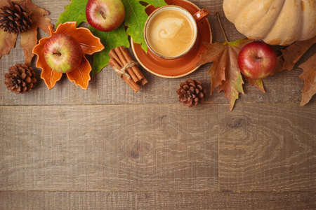 Autumn season concept with coffee cup, apples, pumpkin and fall leaves on wooden table background