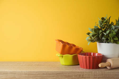 Autumn kitchen interior background with plant and colorful bowls on wooden shelf