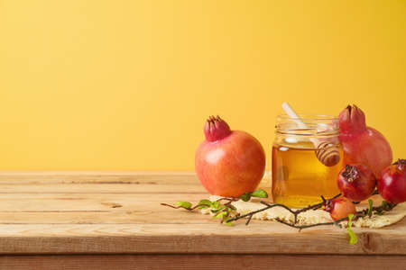 Honey jar and pomegranate on wooden table over yellow background