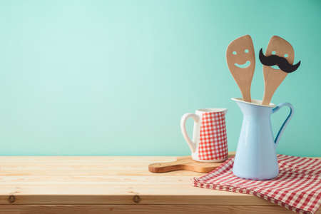 Wooden kitchen counter with kiitchen utensils in jug. Product montage display background or mock up