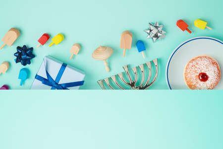 Jewish holiday Hanukkah concept with menorah, sufganiyah, gift box and spinning top over blue background