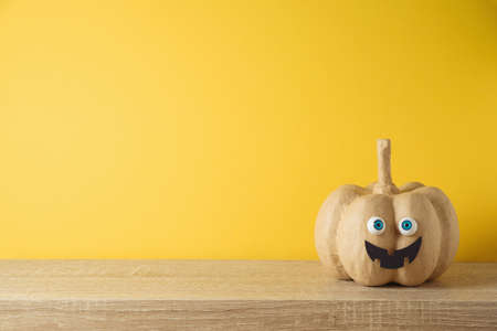 Halloween holiday concept with cute funny pumpkin decor on wooden table over yellow background 免版税图像