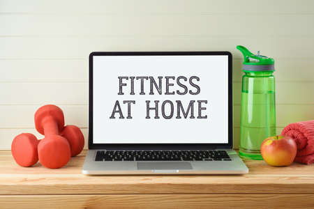 Fitness at home concept with laptop computer, dumbbels and  water bottle on wooden table. Online streaming class for gym workout concept