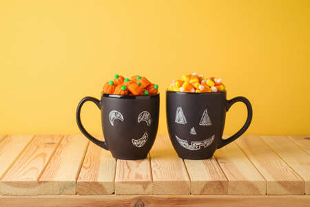 Halloween holiday creative concept with chalkboard coffee mugs and candy corn on wooden table