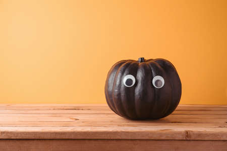 Halloween holiday creative concept with cute funny black pumpkin decor on wooden table over orange background 免版税图像